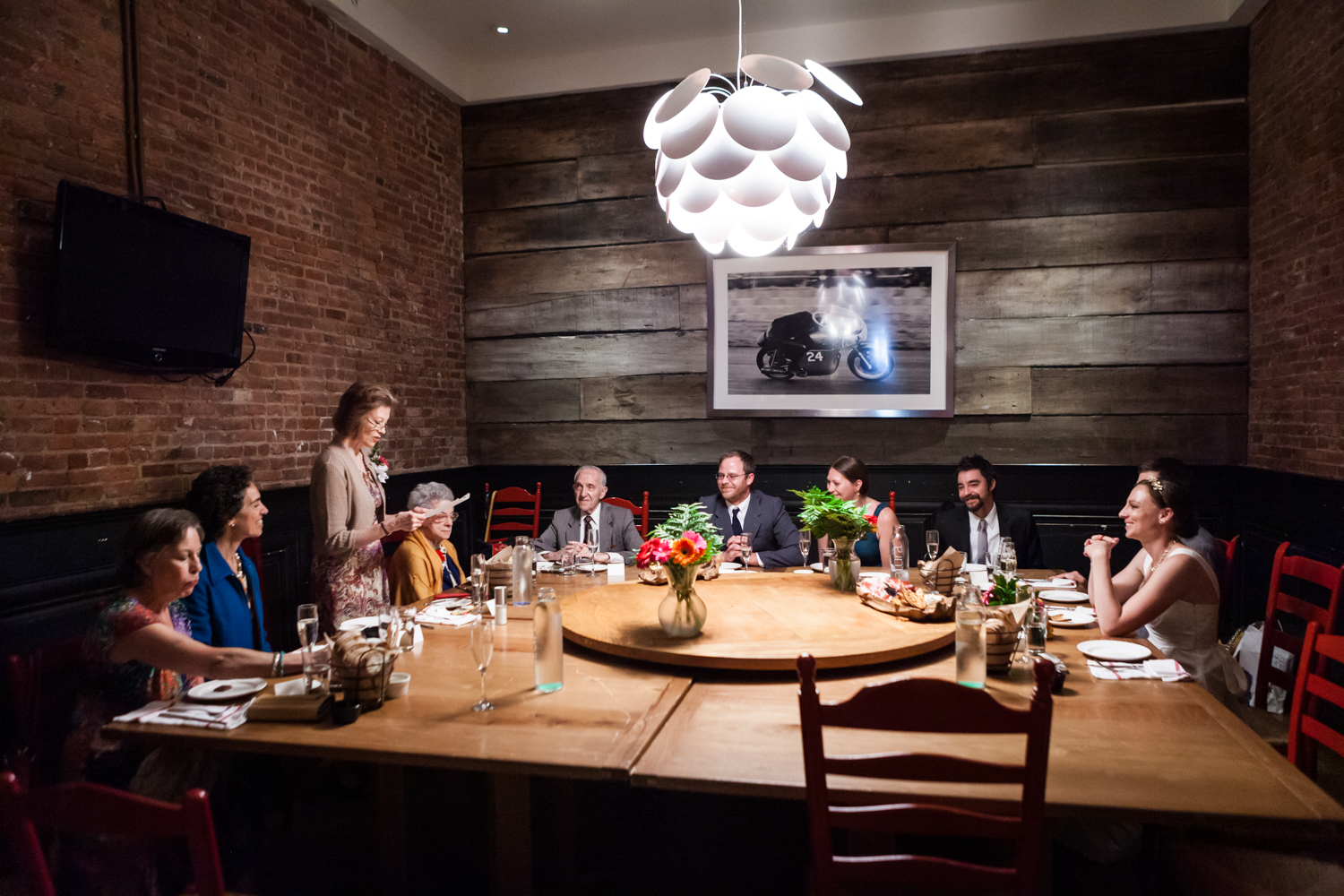 Wide shot of people seated around wooden table at Tribeca reception