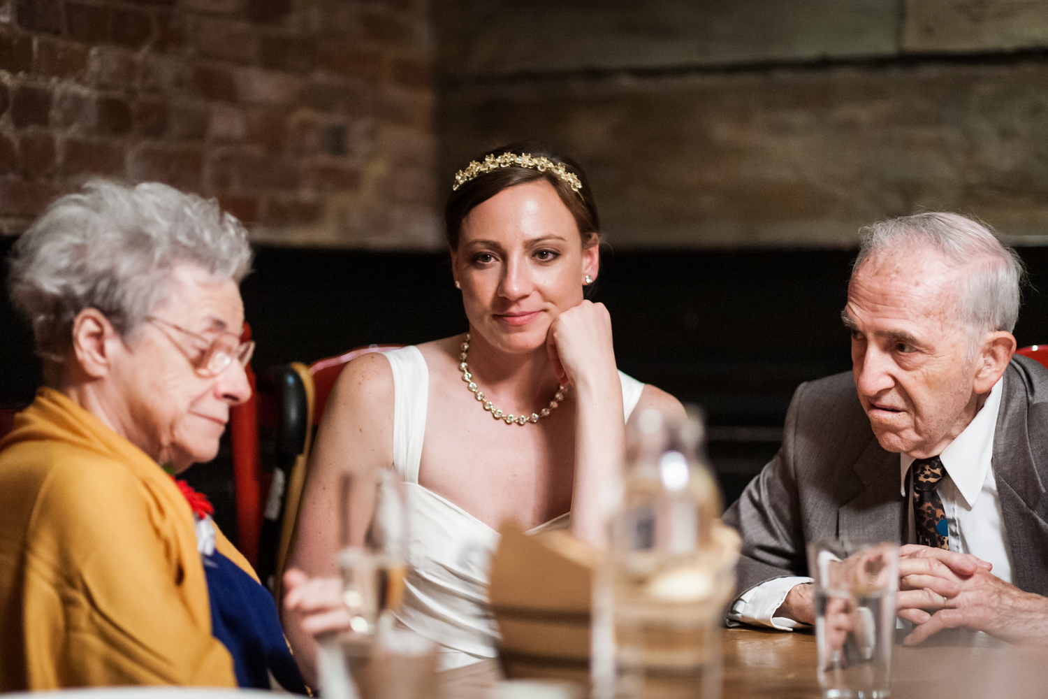 Bride sitting in between her grandparents at Tribeca reception
