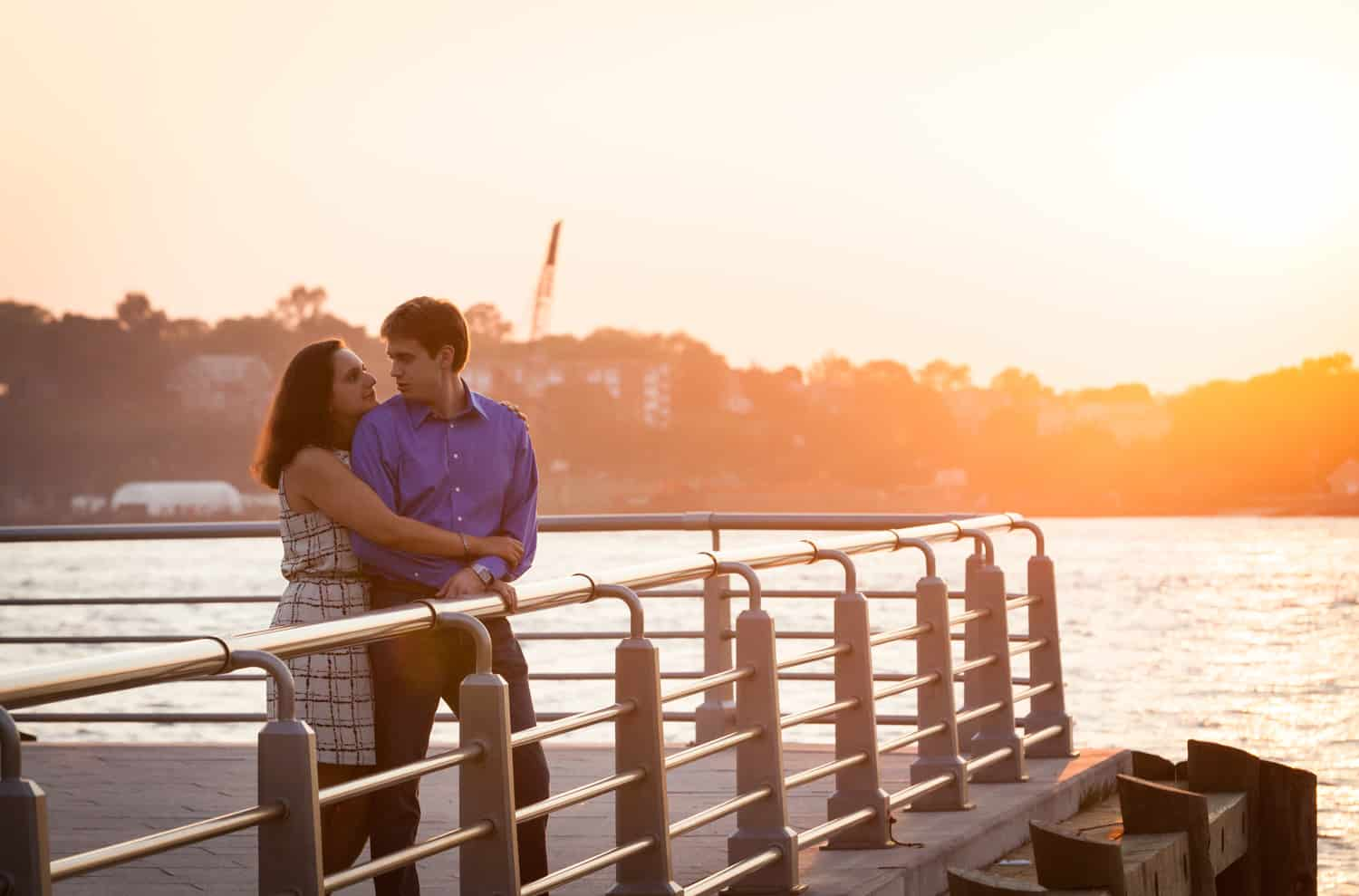 Couple on pier at sunset with Hudson River waterfront in background