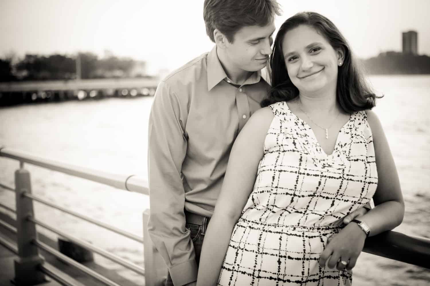 Black and white photo of engaged couple against railing at sunset with Hudson River waterfront in background