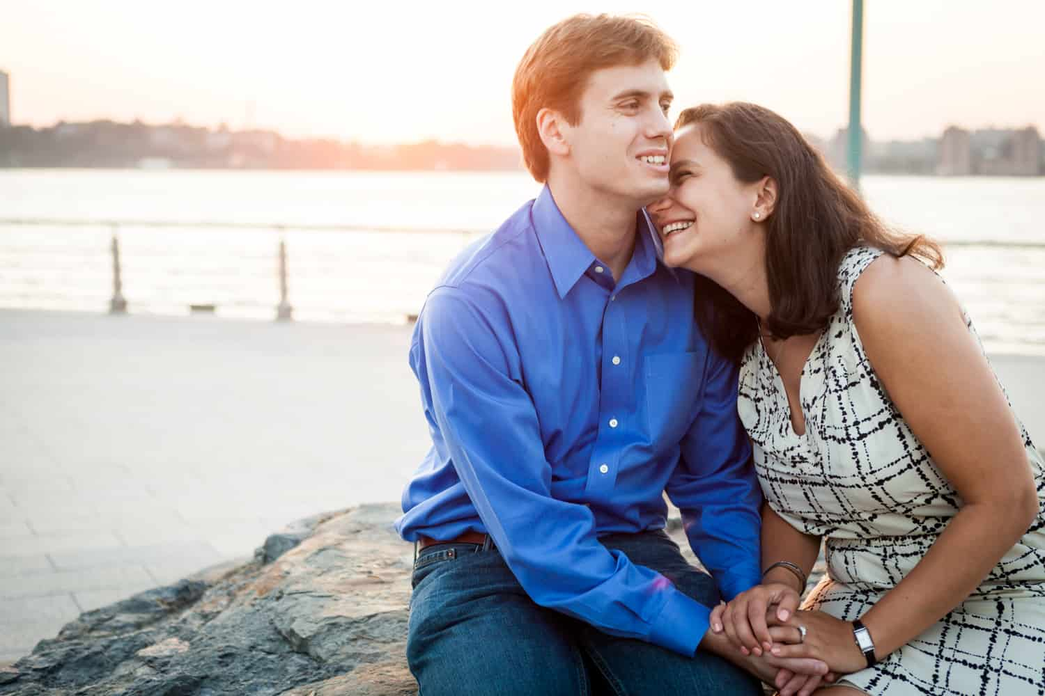 Couple sitting on rock at sunset with Hudson River waterfront in background