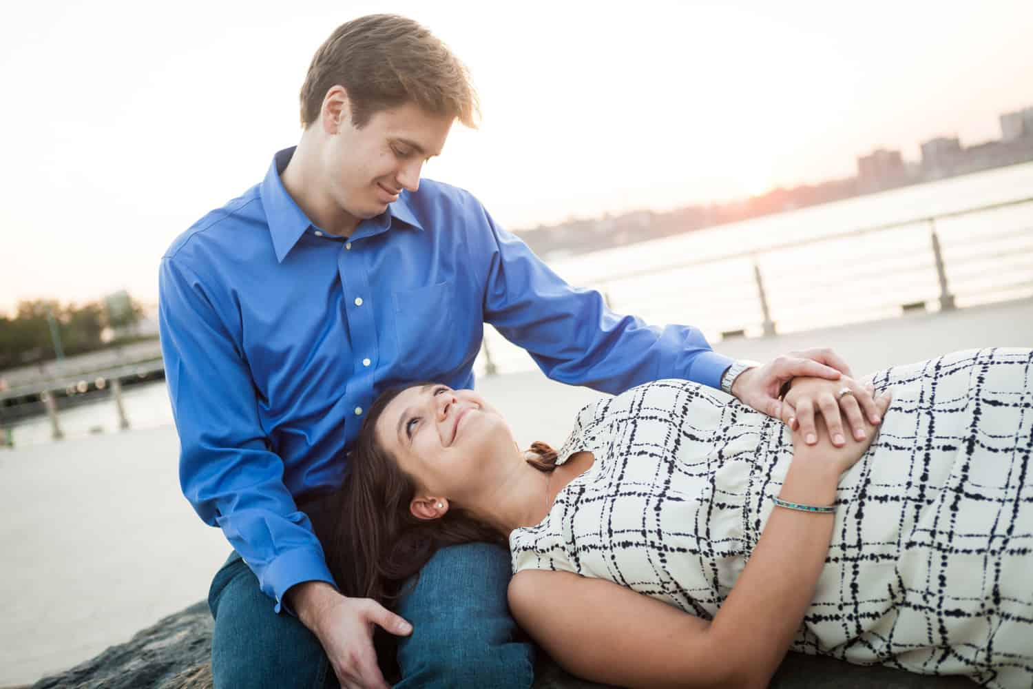 Woman laying down with head in man's lap at sunset with Hudson River waterfront in background