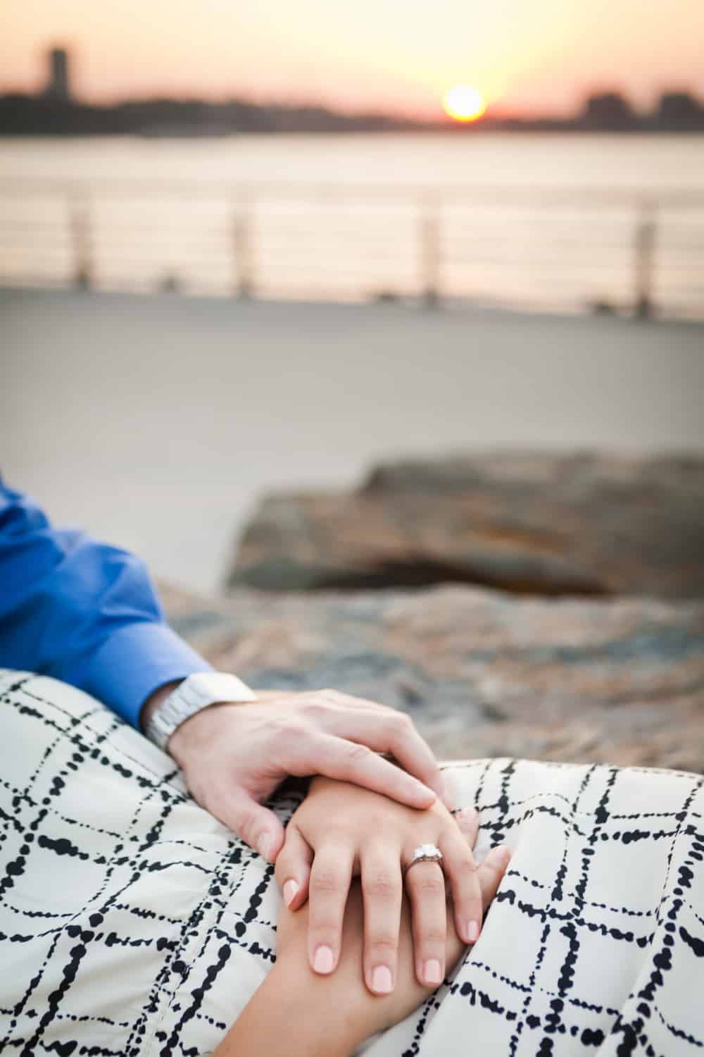 Close up on couple's hands with woman wearing engagement ring and Hudson River waterfront at sunset