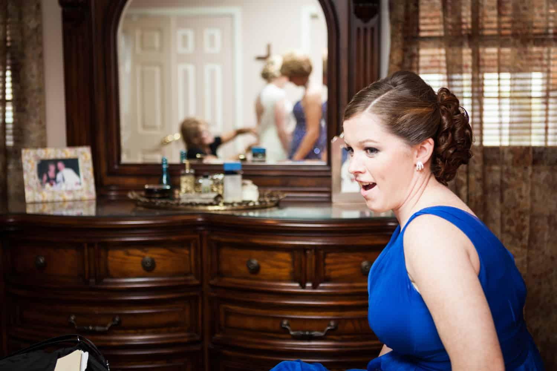 Bridesmaid looking at bride getting into dress