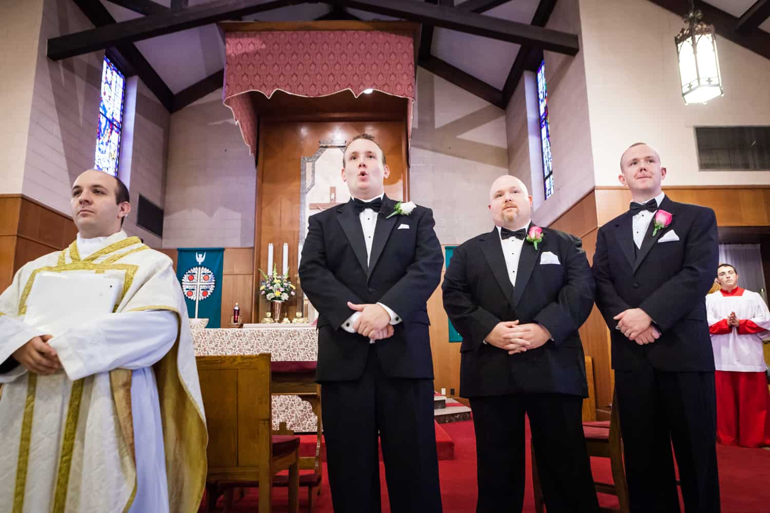 Groom and groomsmen waiting for bride to walk down the aisle