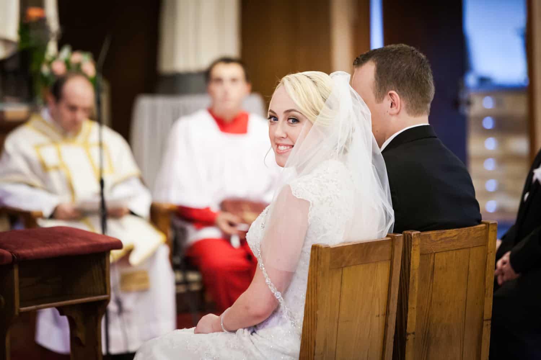Bride looking over shoulder during wedding ceremony