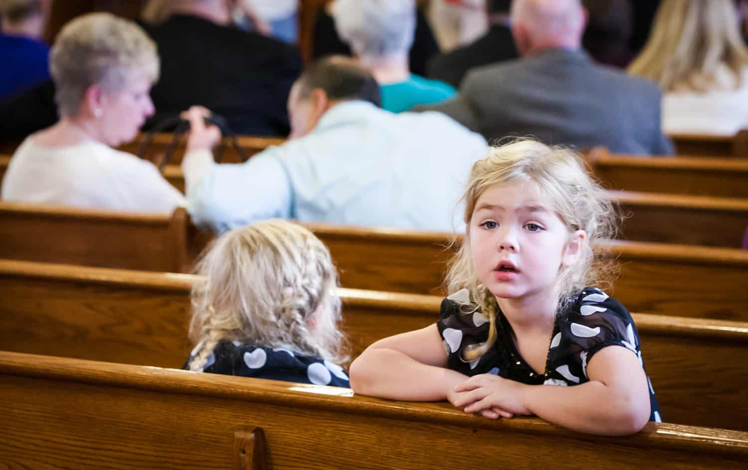 Little girl turned around in pew during wedding ceremony