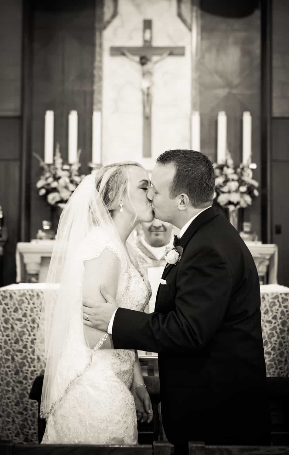 Black and white photo of bride and groom kissing after ceremony