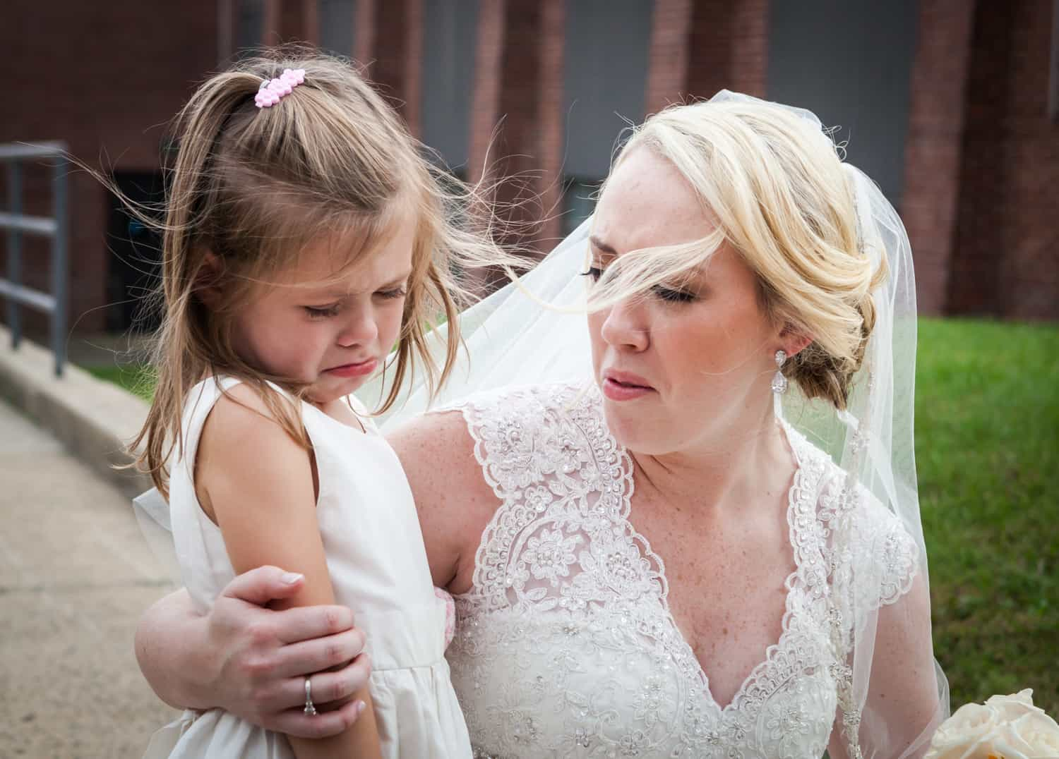 Bride consoling crying little girl after wedding ceremony