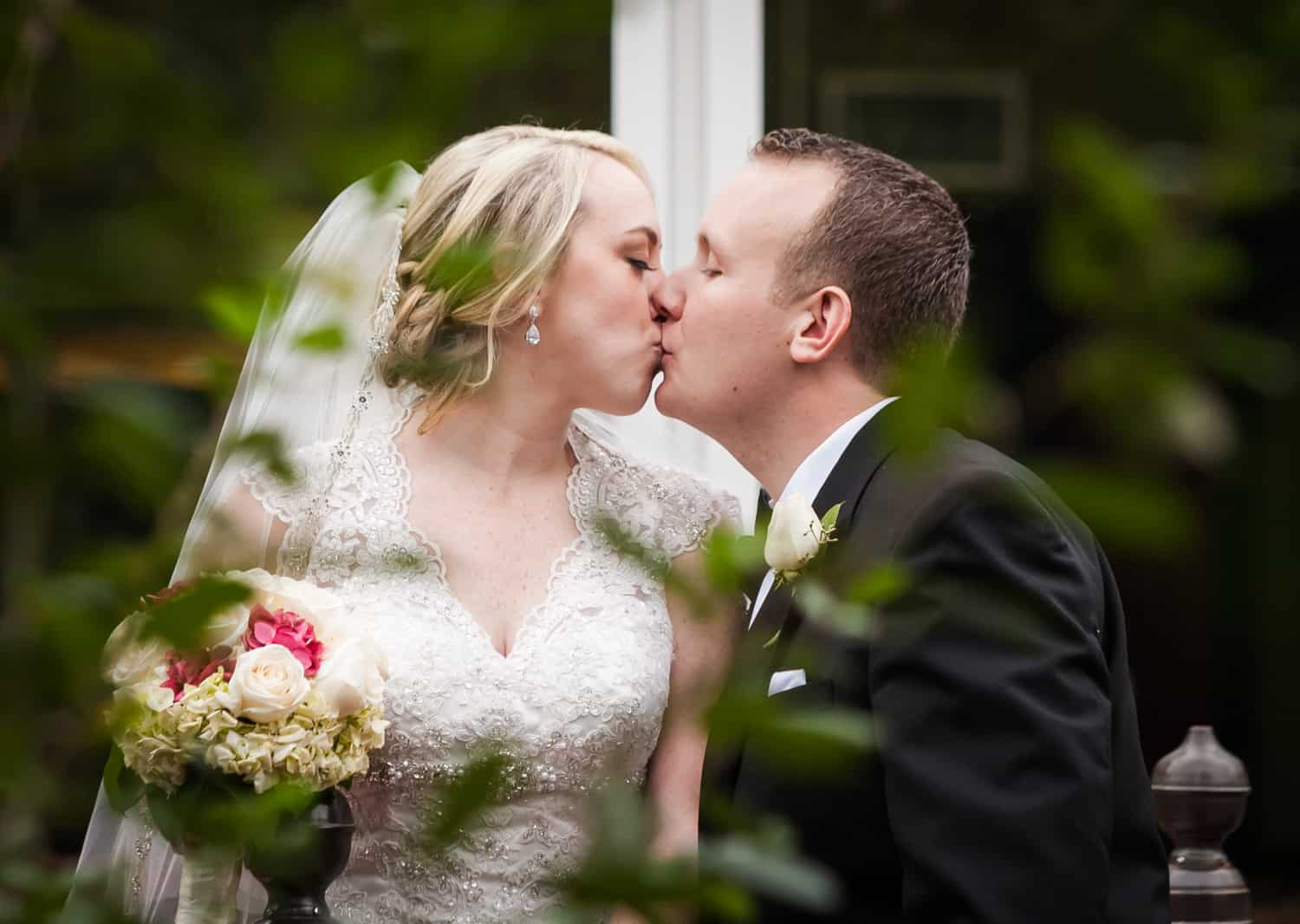 View through branches of bride and groom kissing at a Nicotra's Ballroom wedding
