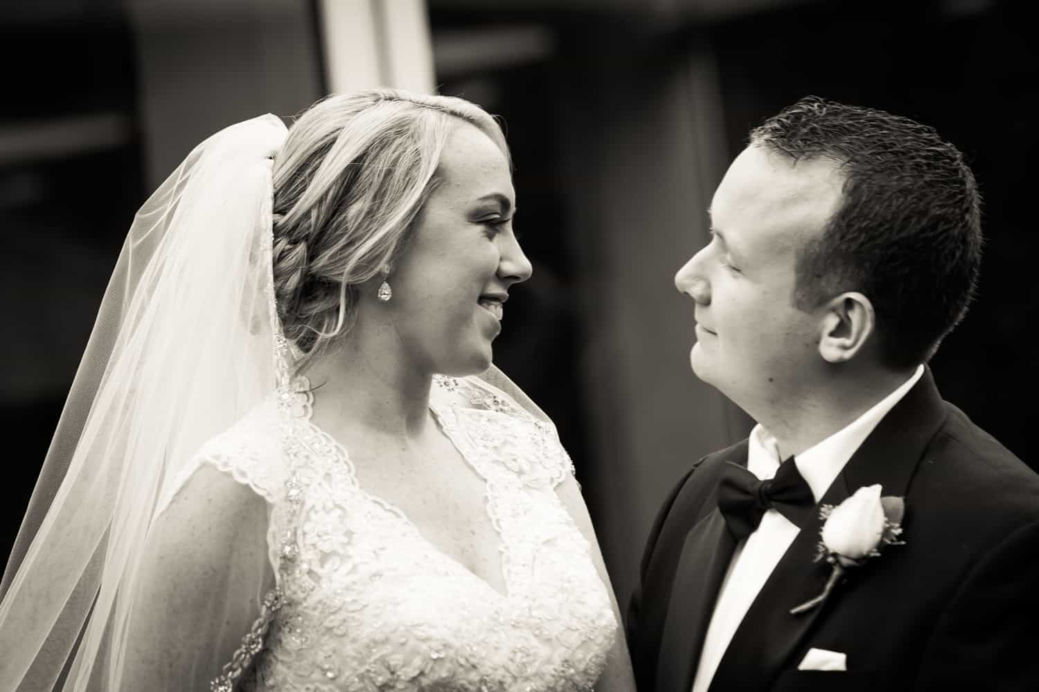 Black and white photo of bride and groom looking at each other