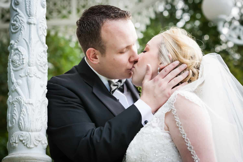 Bride and groom kissing in gazebo at a Nicotra's Ballroom wedding