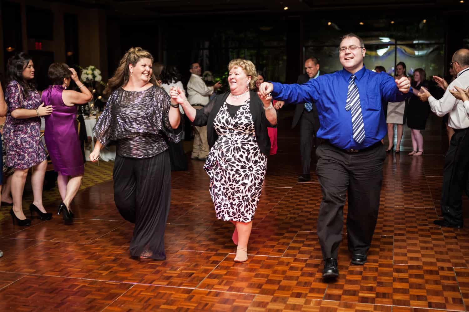 Three guests in line dance at a Nicotra's Ballroom wedding