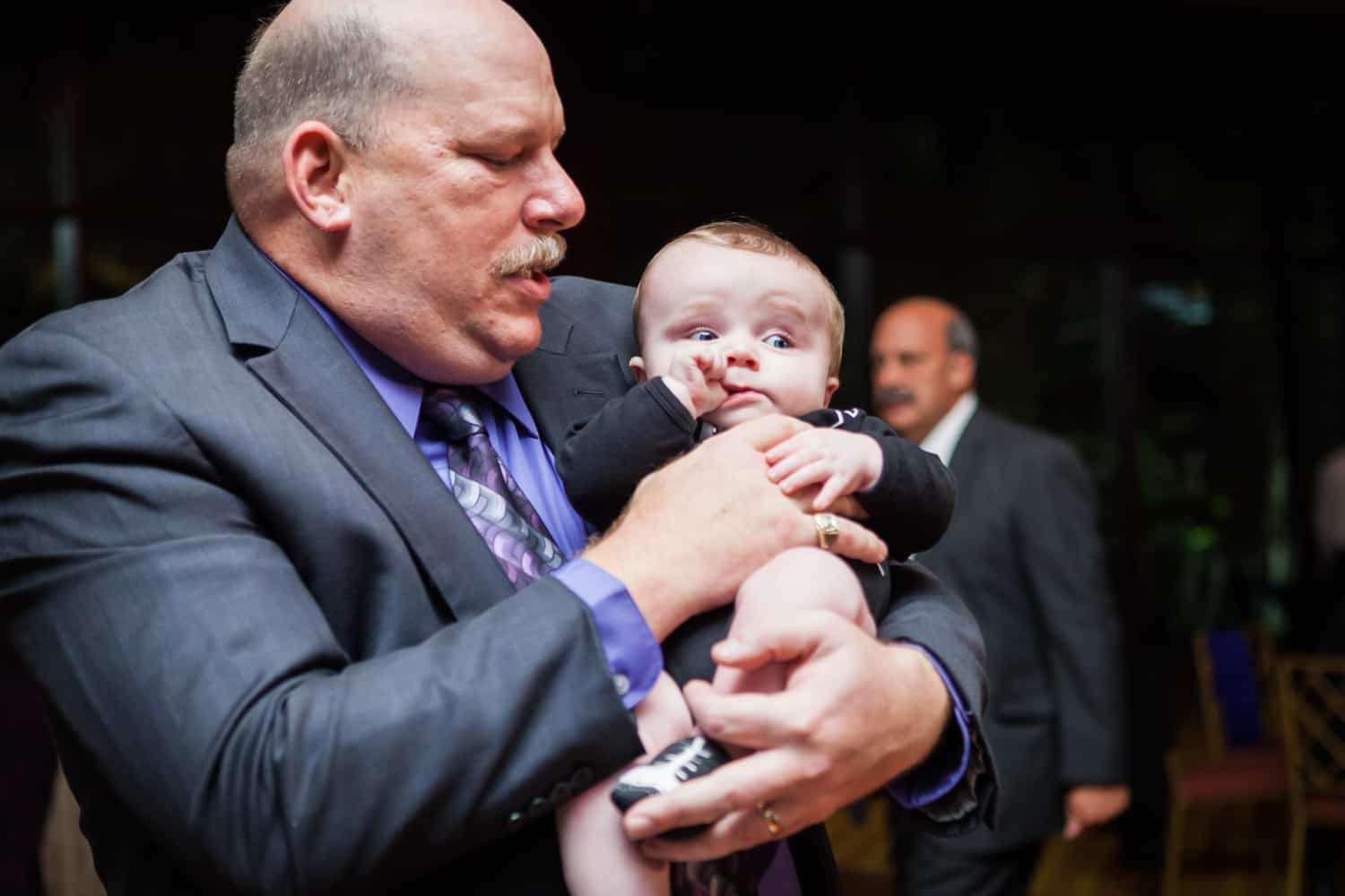 Grandfather holding little baby at a Nicotra's Ballroom wedding