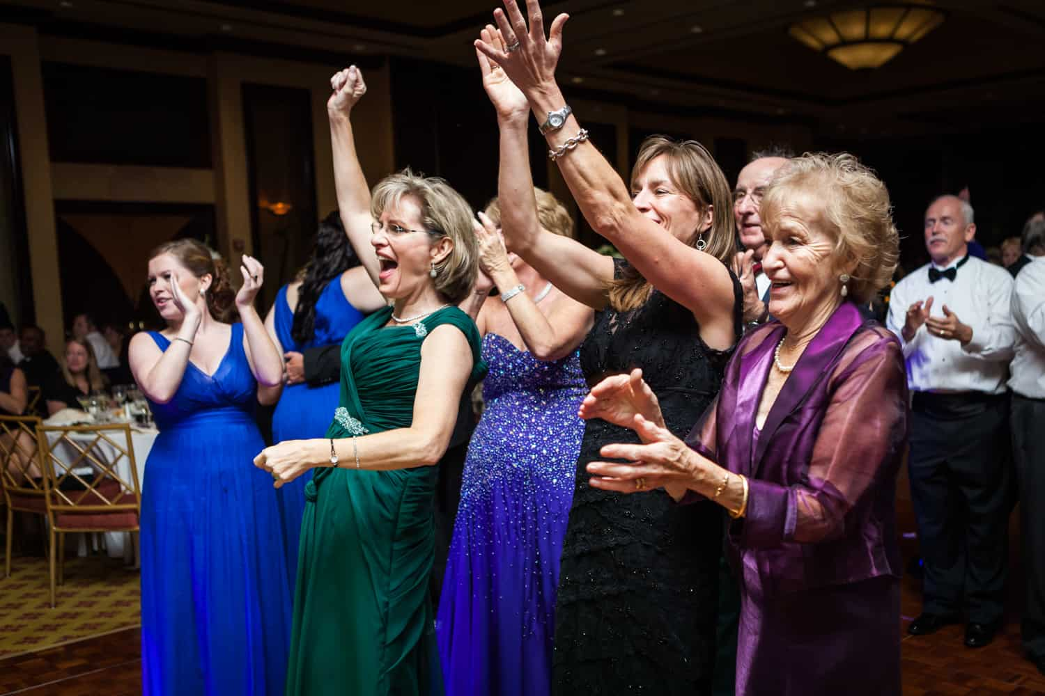 Guests cheering with arms raised at a Nicotra's Ballroom wedding