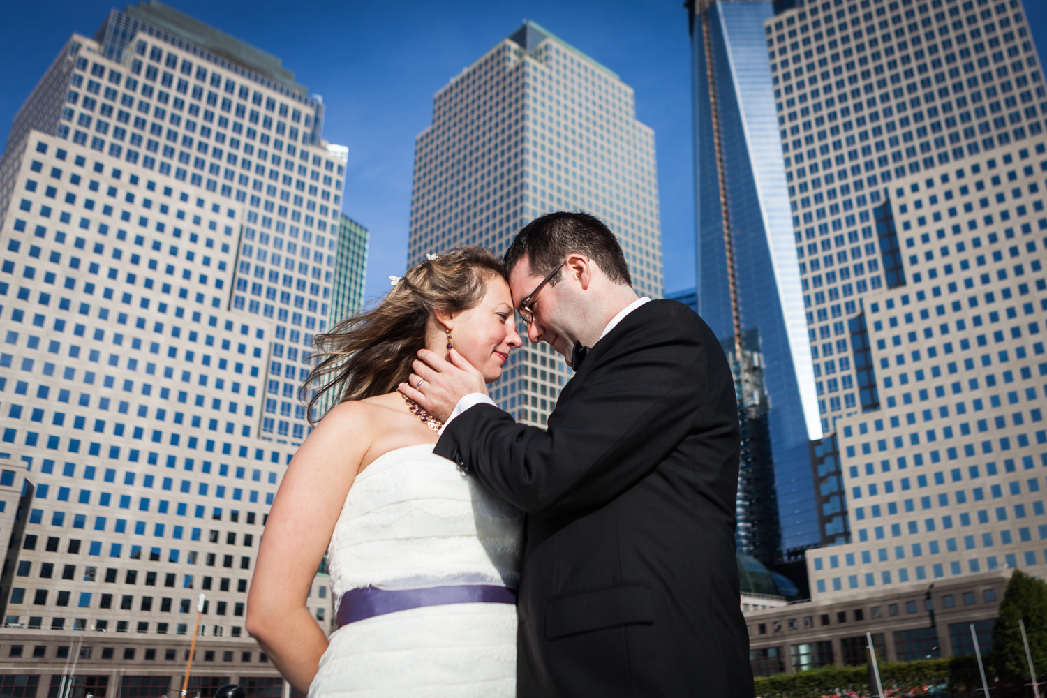 Bride and groom standing in front of downtown NYC buildings