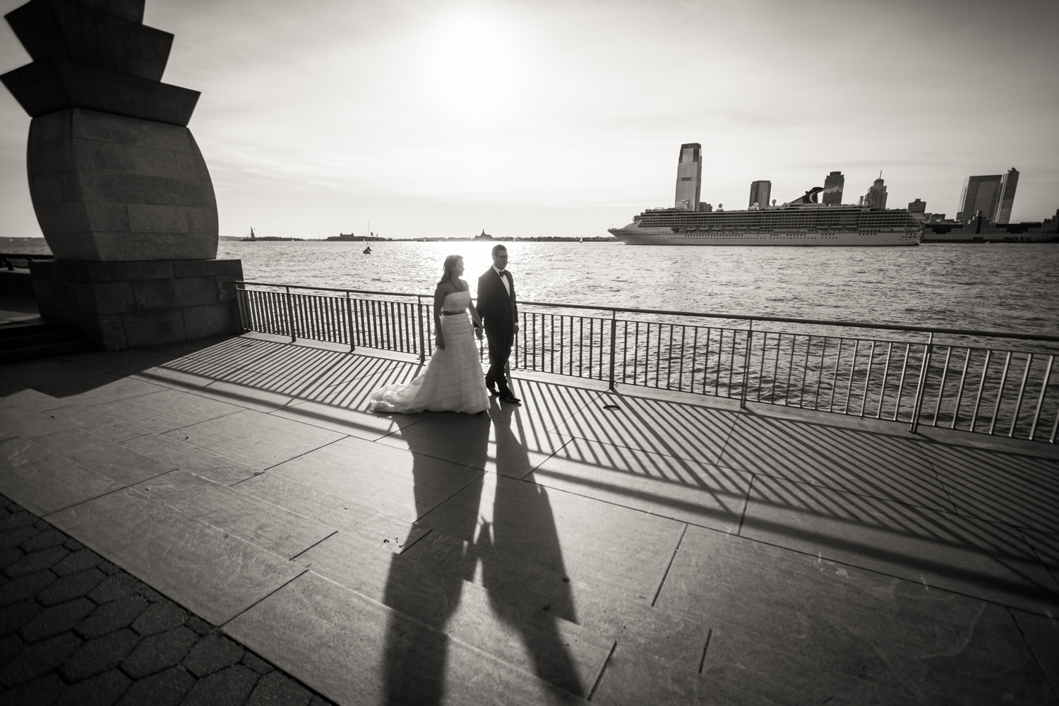 Black and white photo of bride and groom walking in Rockefeller Park