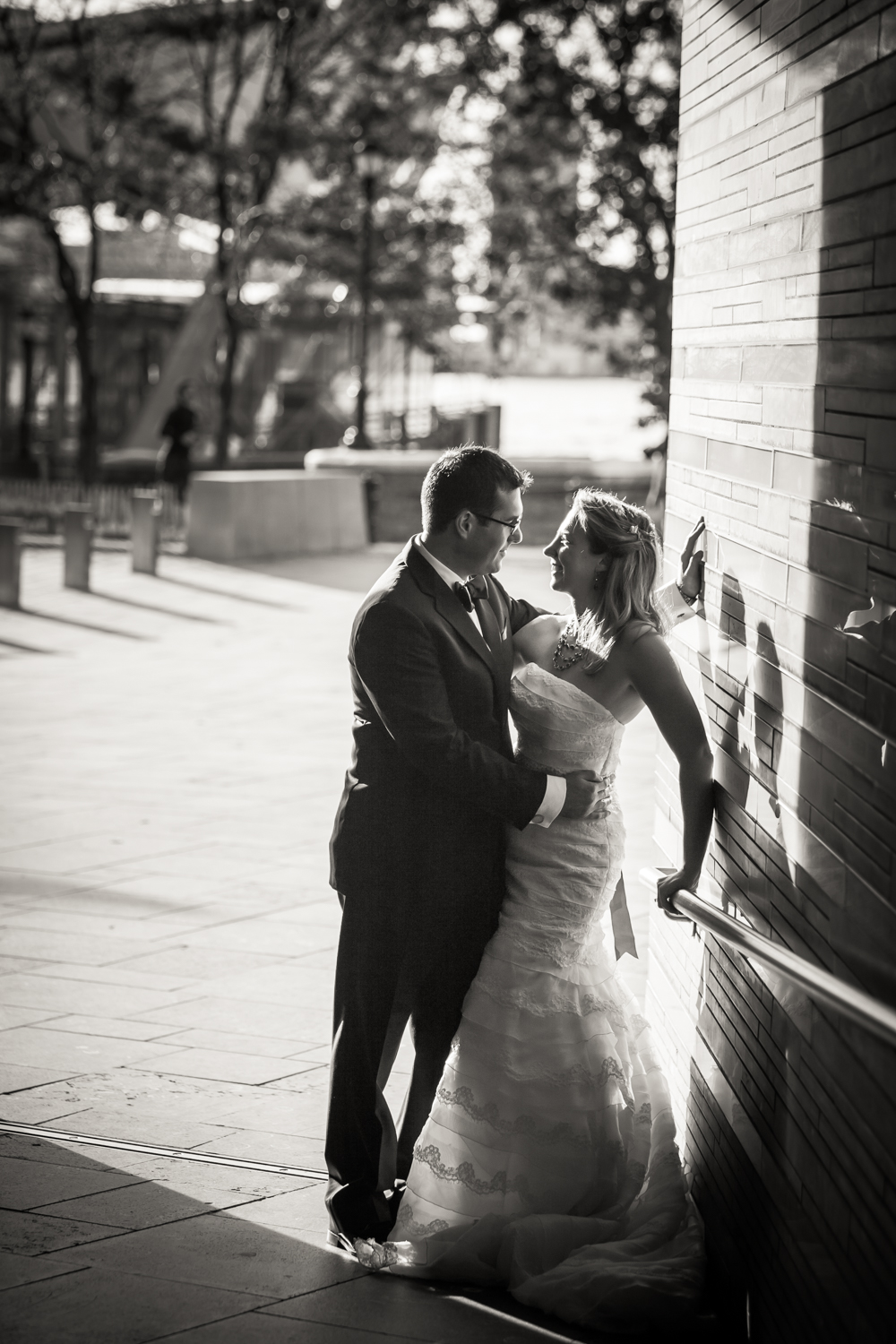 Black and white photo of groom and bride against wall