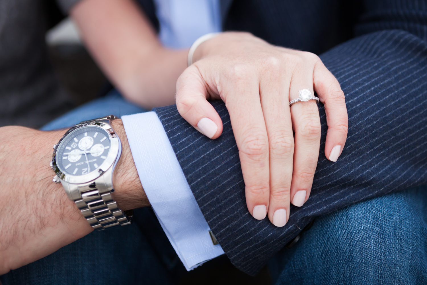 Close up of woman's hand wearing engagement ring on man's arm