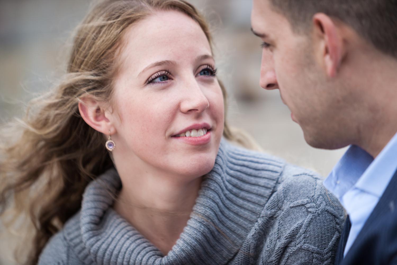 Close up of woman looking at man during a Brooklyn Bridge Park engagement shoot