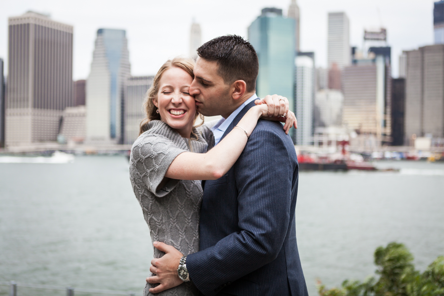 Man kissing woman on the side of her face with NYC skyline in background