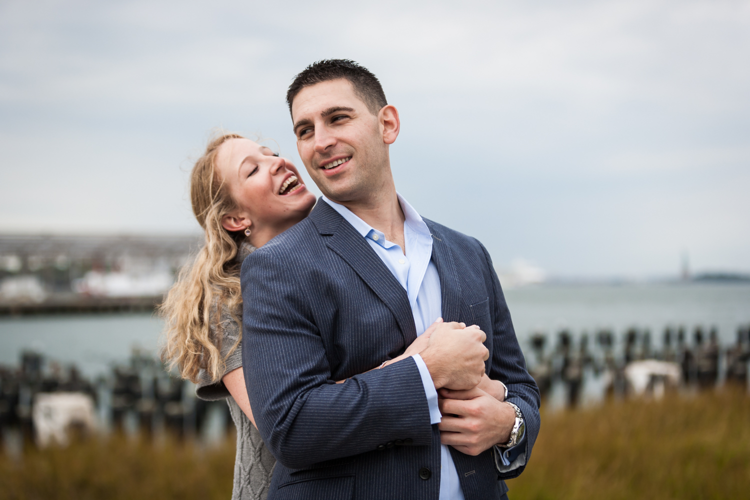 Woman hugging man from behind during a Brooklyn Bridge Park engagement shoot