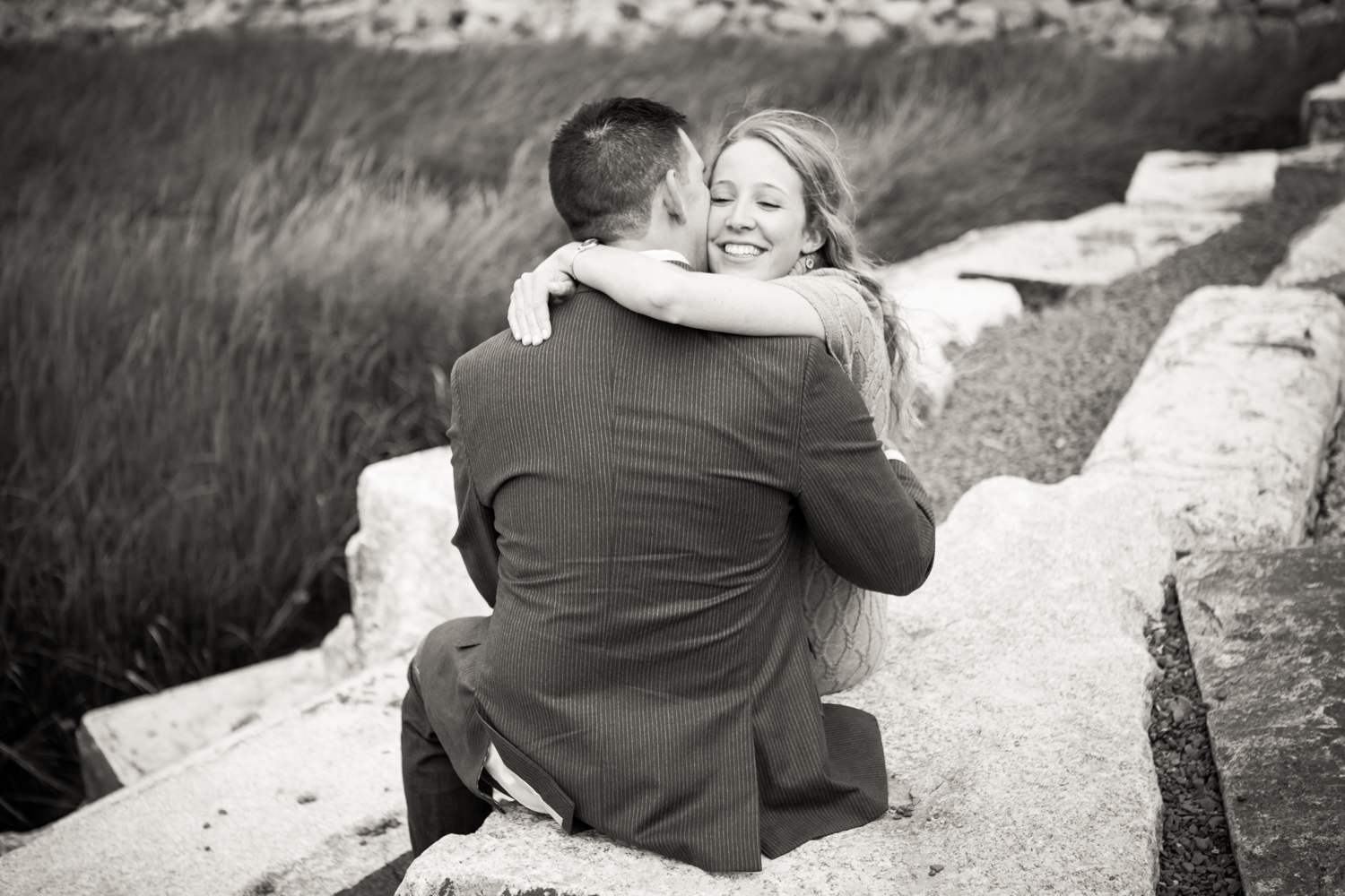 Black and white photo of couple hugging while sitting on rock steps
