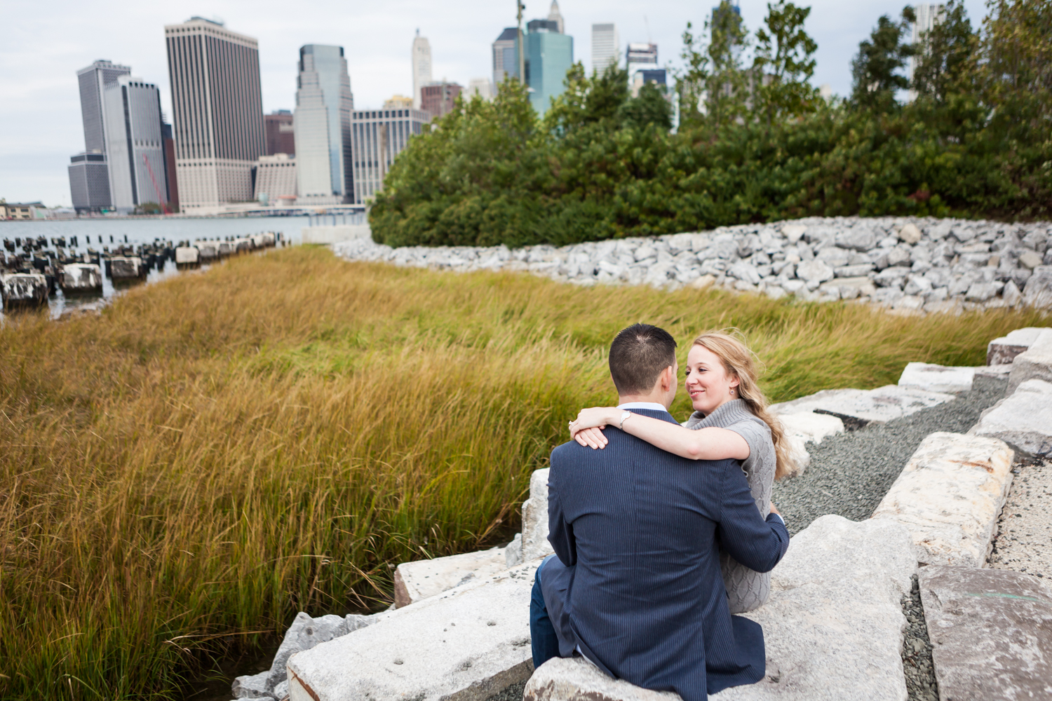 Couple hugging in Brooklyn Bridge Park with NYC skyline in background