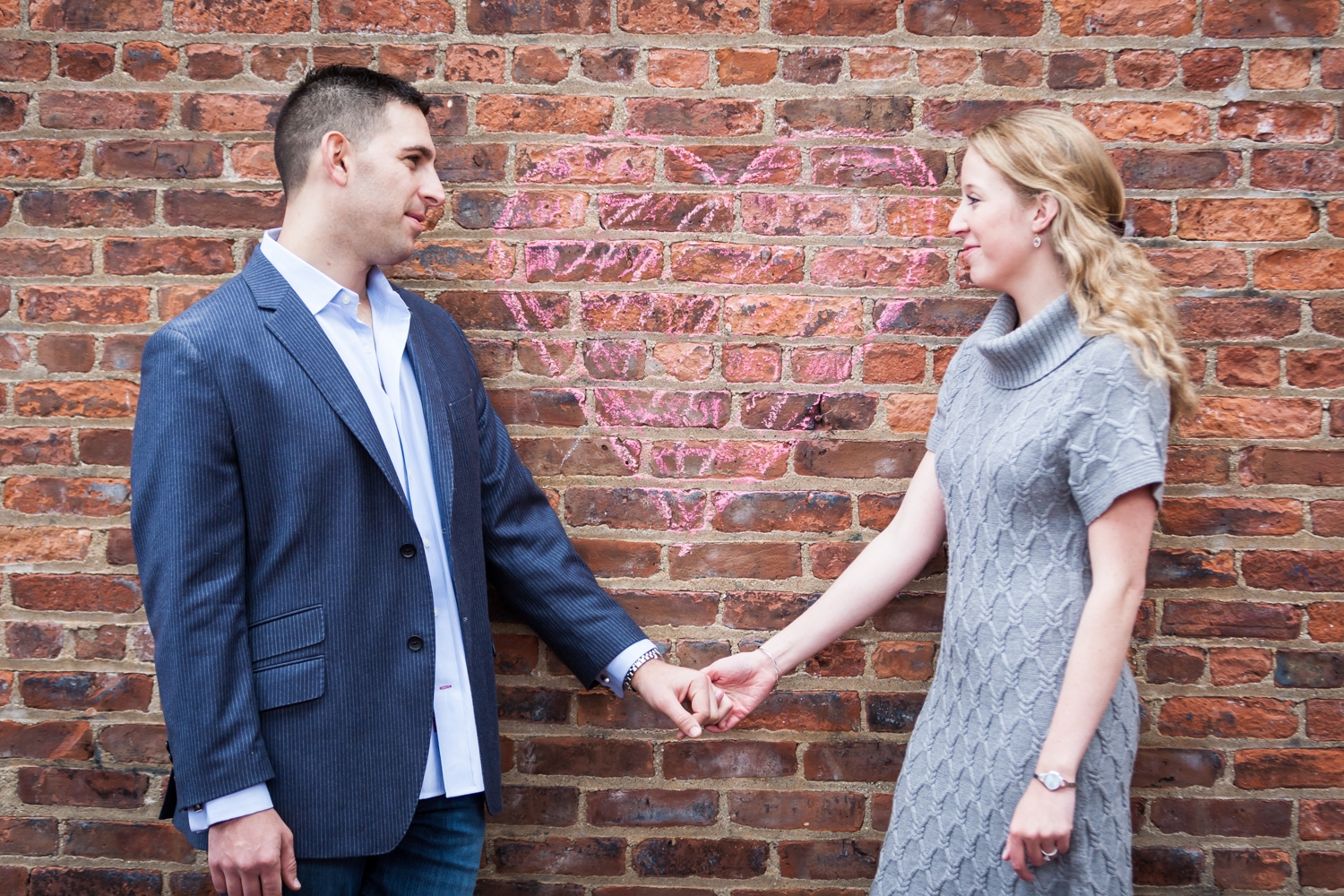Couple holding hands against brick wall underneath chalk heart