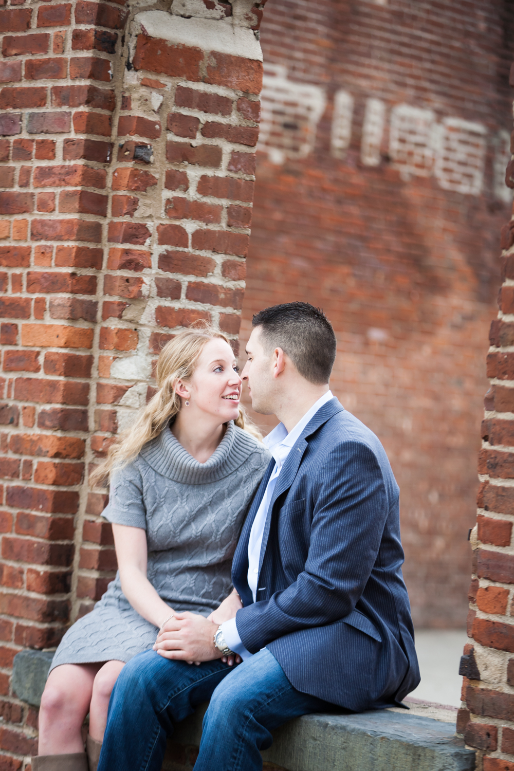 Couple kissing in brick archway during a Brooklyn Bridge Park engagement shoot