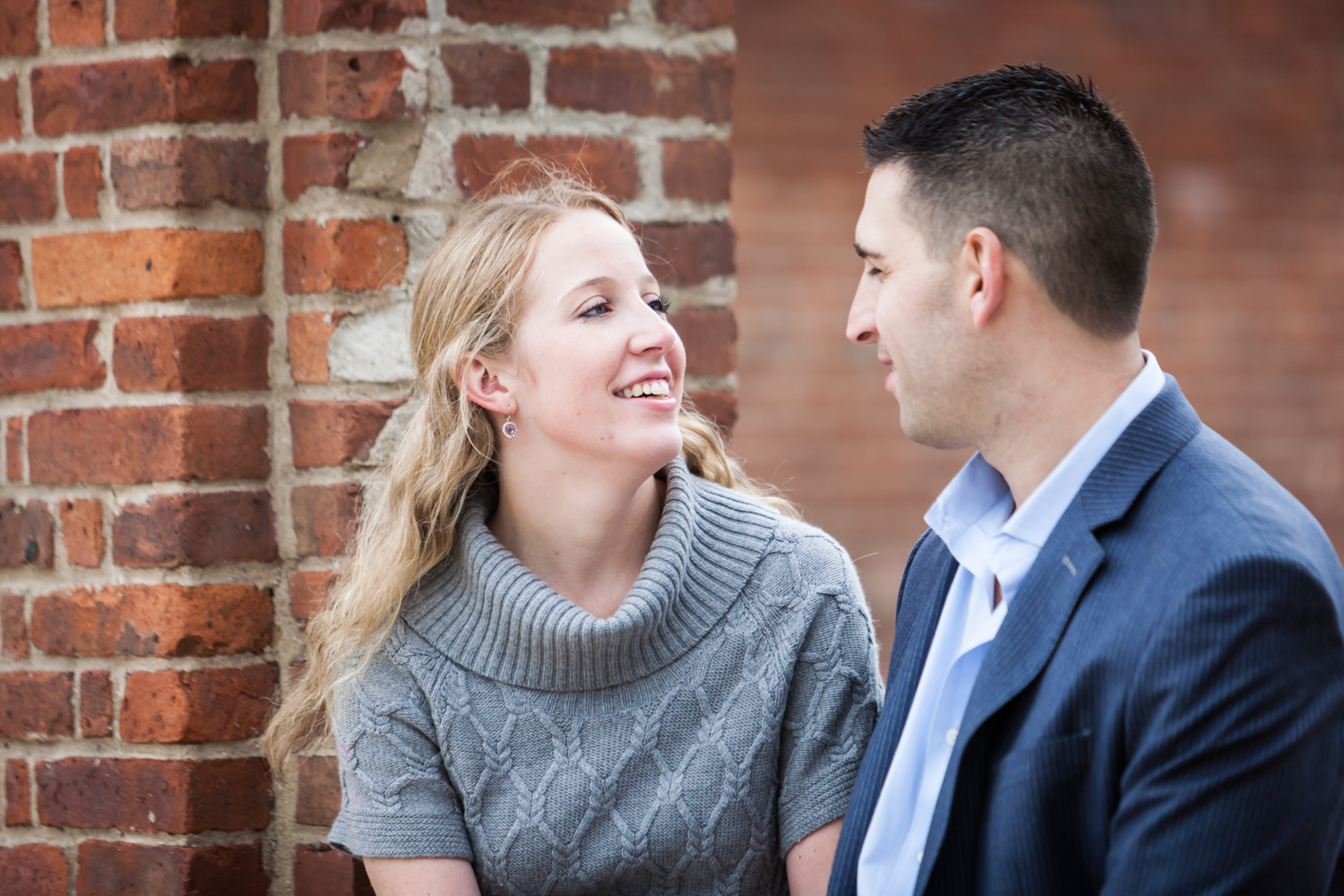 Couple sitting in brick archway during a Brooklyn Bridge Park engagement shoot