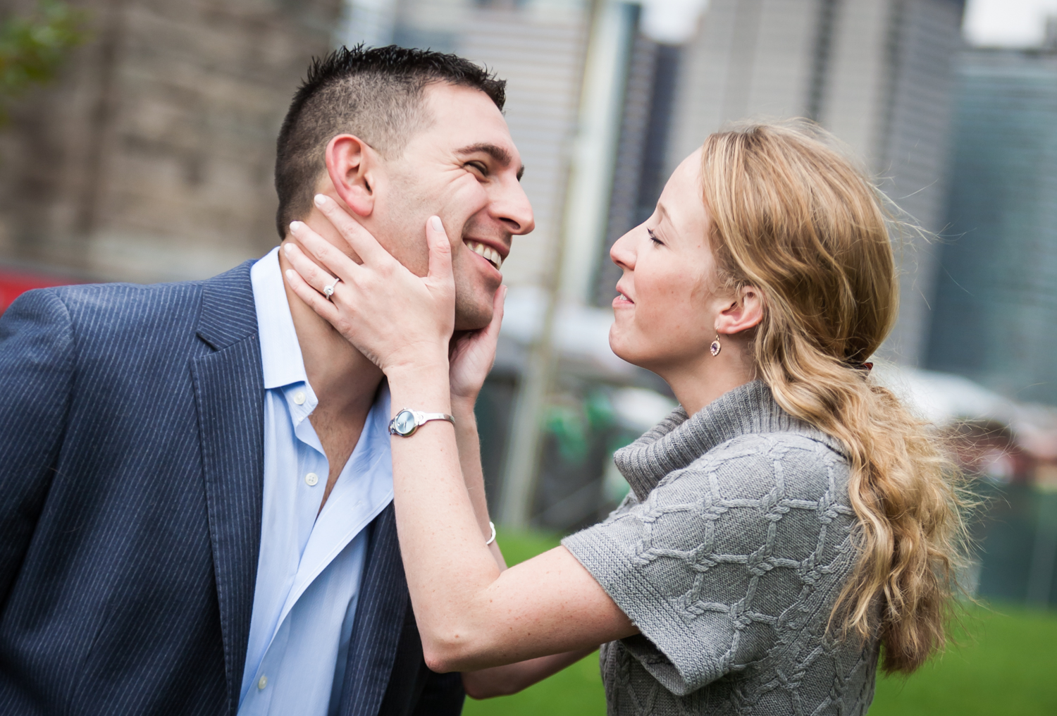 Woman touching man's face during a Brooklyn Bridge Park engagement shoot