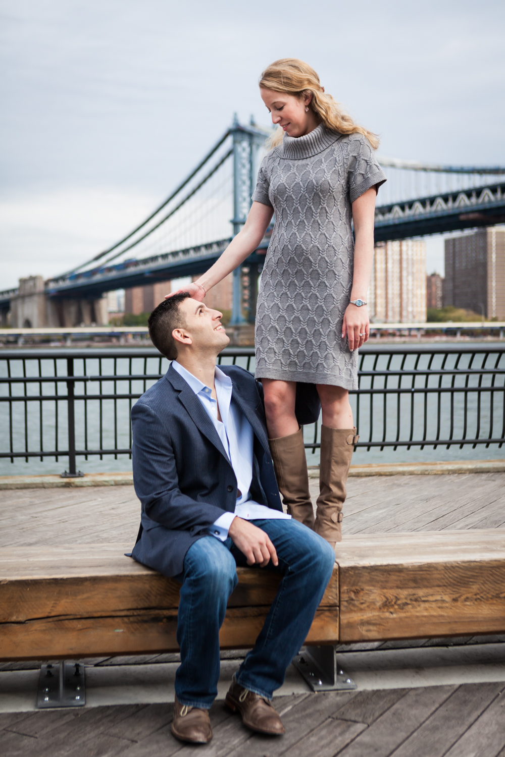 Man sitting on bench looking up at woman during a Brooklyn Bridge Park engagement shoot