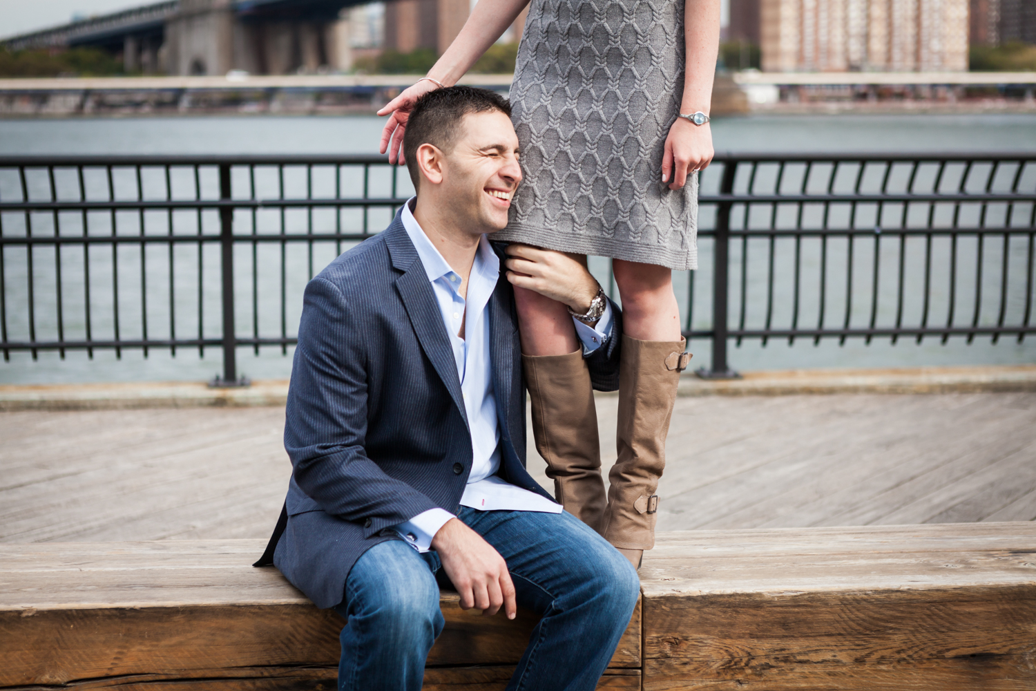 Man sitting on bench and holding on to woman's legs during a Brooklyn Bridge Park engagement shoot