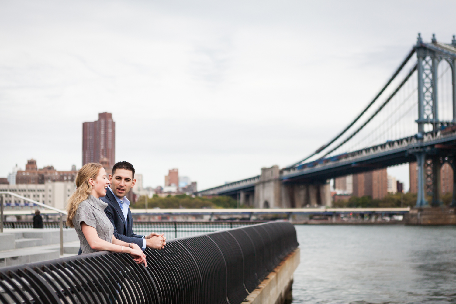 Couple standing by railing looking at East River during a Brooklyn Bridge Park engagement shoot