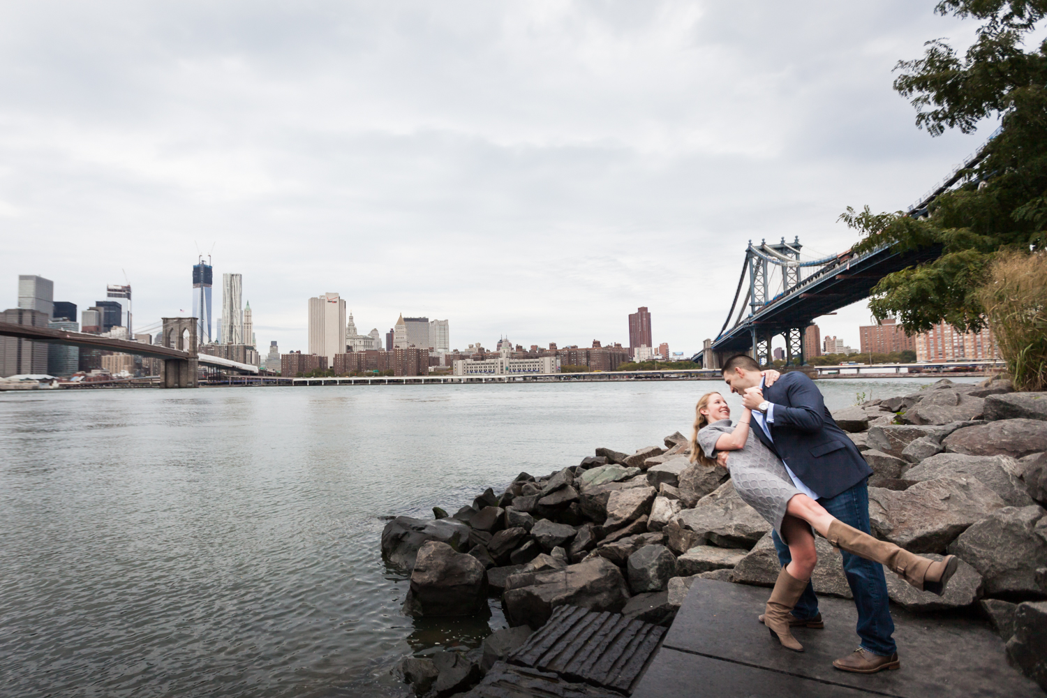 Man dipping woman while dancing with East River and bridges in background