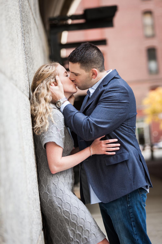 Woman kissing man wall during a Brooklyn Bridge Park engagement shoot