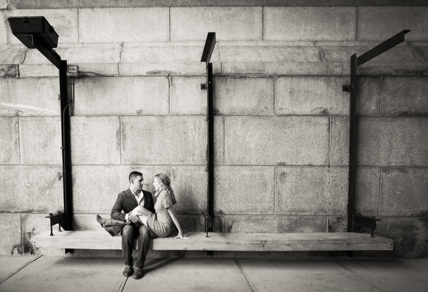 Black and white photo of woman sitting on bench with legs in man's lap
