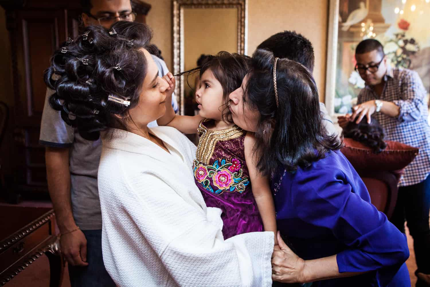 Bride in curlers holding little girl and woman kissing little girl on cheek