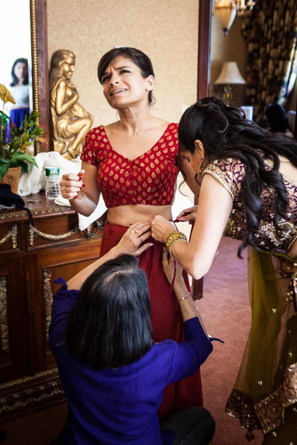Two women fitting bride into traditional Indian sari