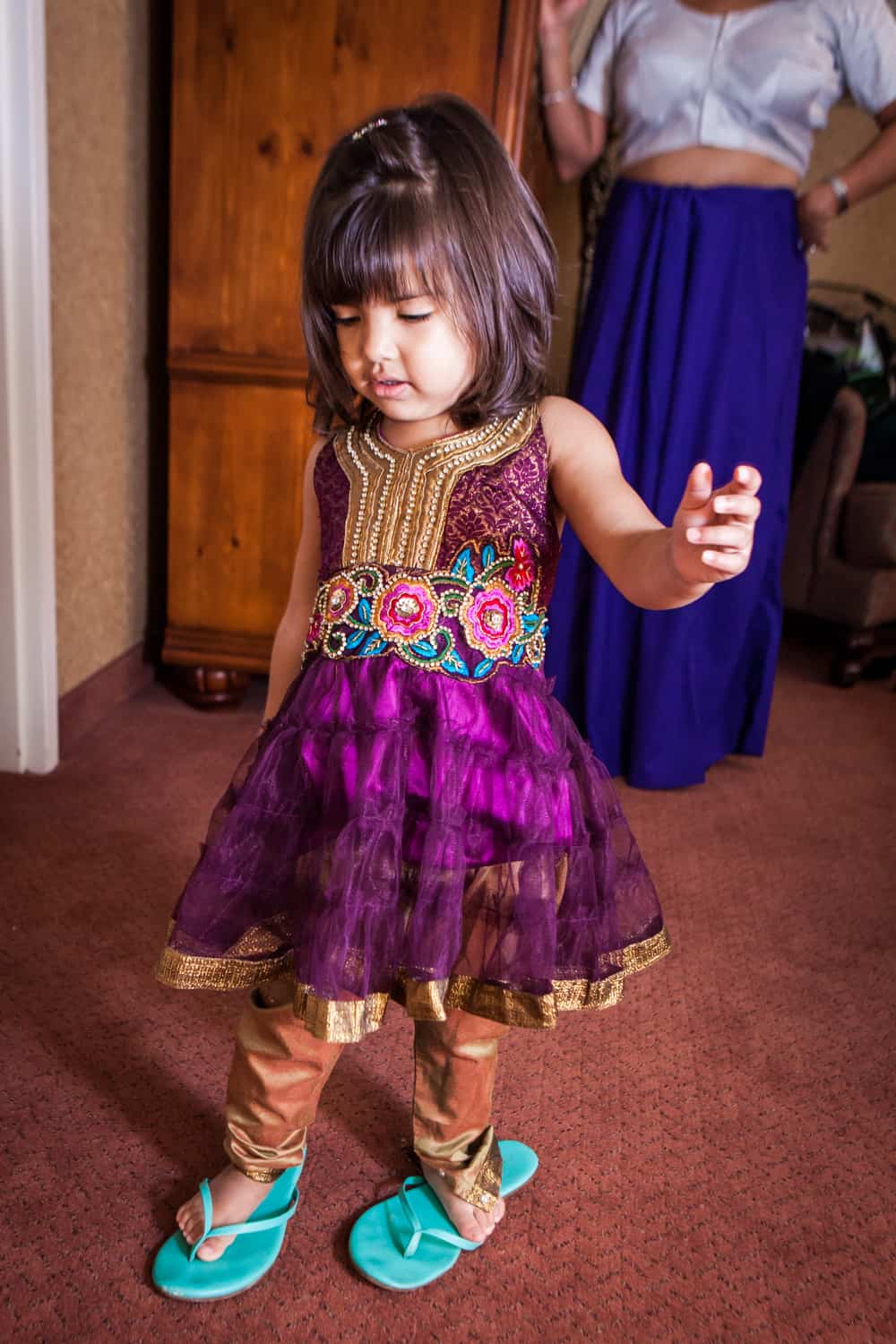Little girl wearing traditional Indian attire and her mother's flip flops