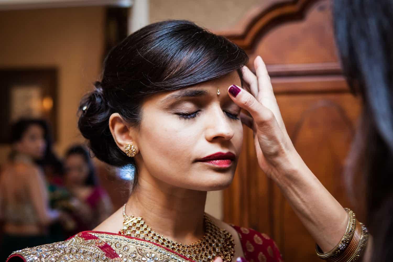Hand applying bindi to bride