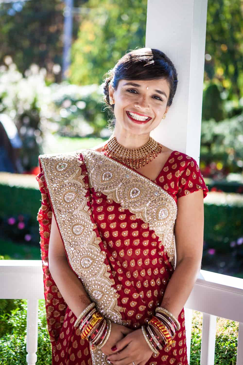 Bride in gazebo wearing red traditional sari at an East Wind Inn wedding