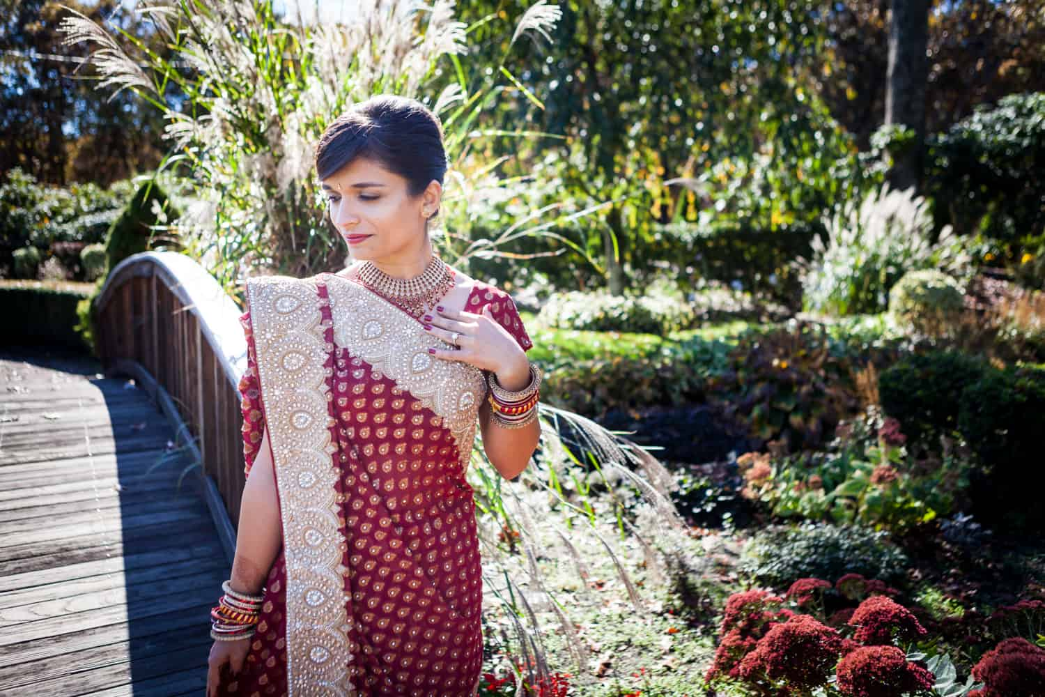 Bride in garden wearing red traditional sari at an East Wind Inn wedding