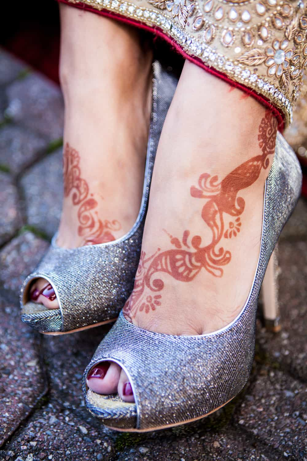 Close up on bride's feet wearing silver high heels and Indian henna design on skin