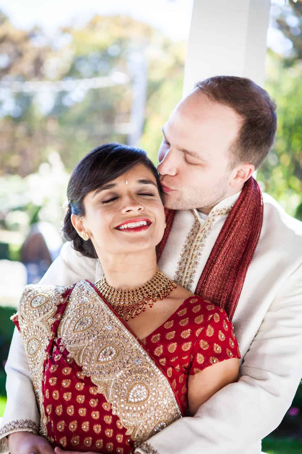 Groom kissing bride while wearing traditional Indian attire Bride and groom wearing traditional wedding attire at an East Wind Inn wedding