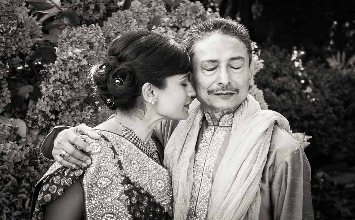 Black and white photo of bride and father wearing traditional Indian attire with closed eyes