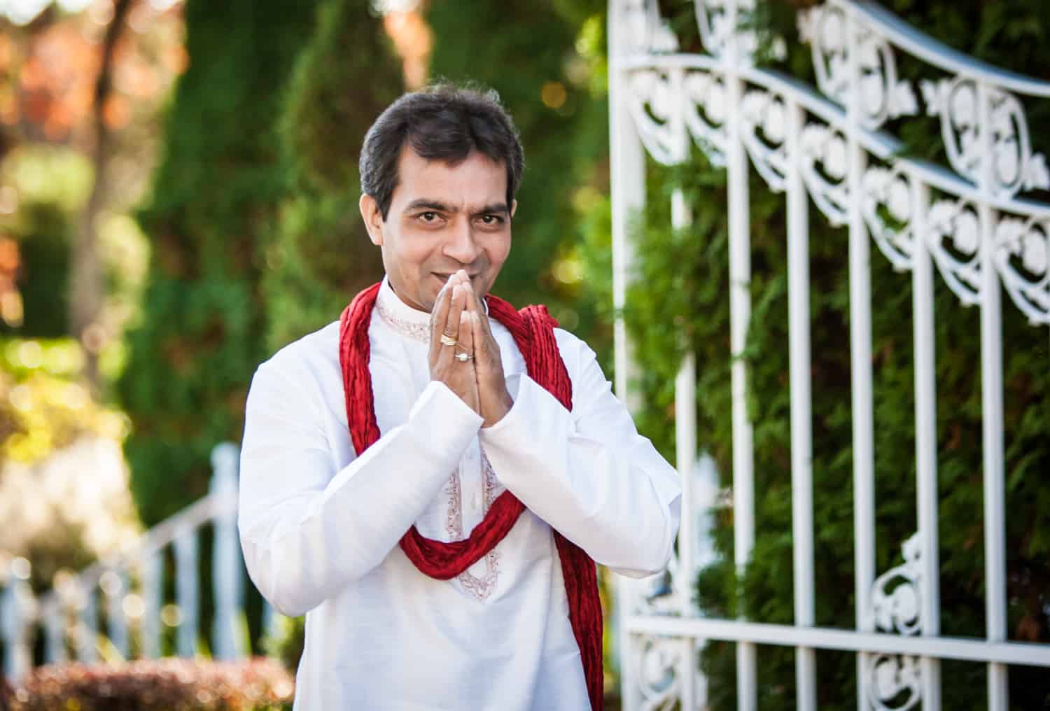 Man with praying hands and traditional Indian attire in front of gate