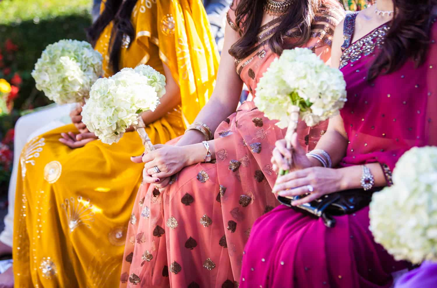 Close up on bridesmaids wearing colorful saris and holding bouquets