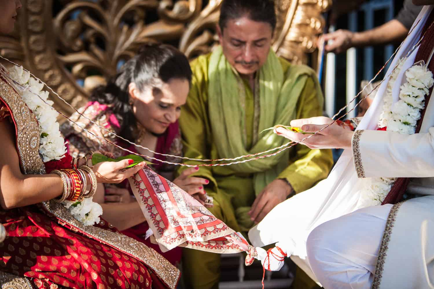 Bride and groom with parents during traditional Hindu wedding ceremony